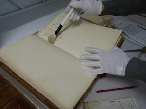 Surface dust being removed from the pages of a case book with a brush.